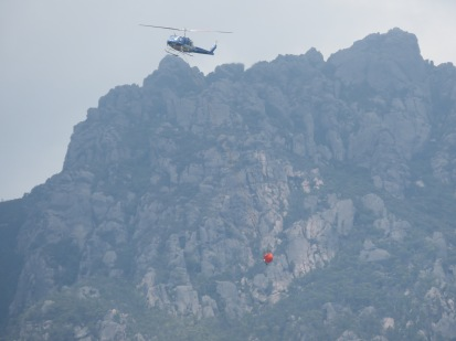 helicopter with the red fire water bucket on its way to or from fighting a bush fire